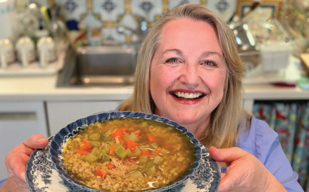 Mary's holds a bowl of chicken soup that was made with bone broth.