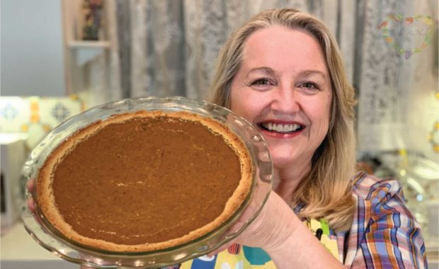 Mary holding a baked pumpkin pie.