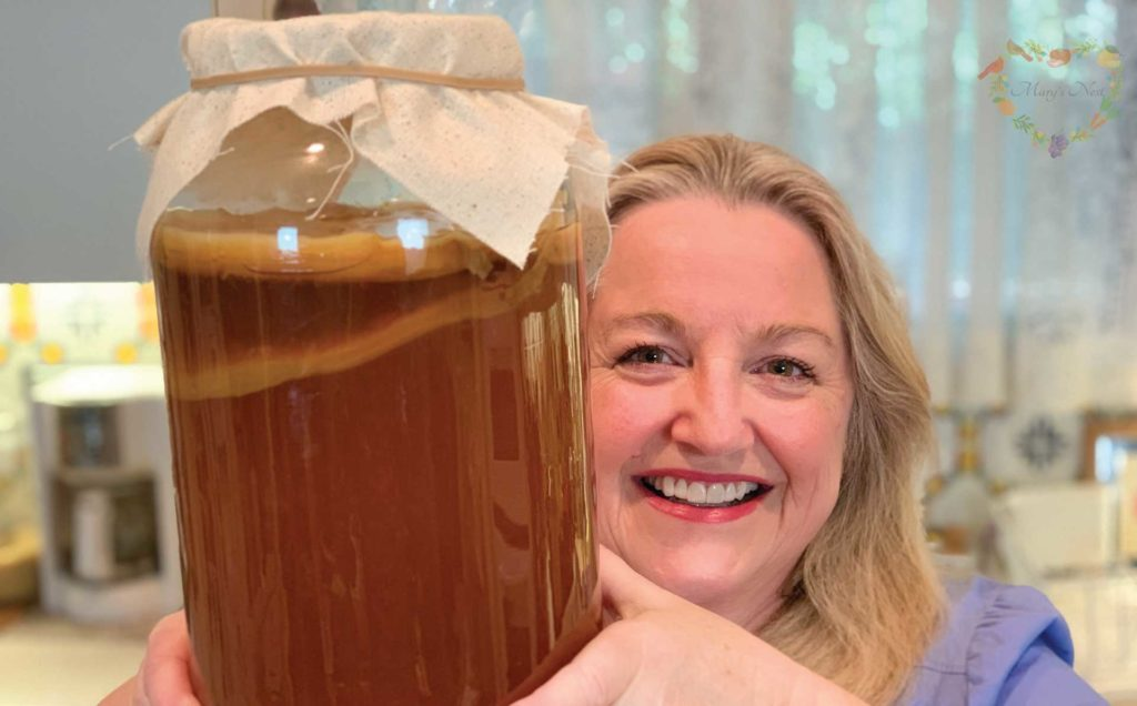 Mary holding a jar with a Kombucha SCOBY.