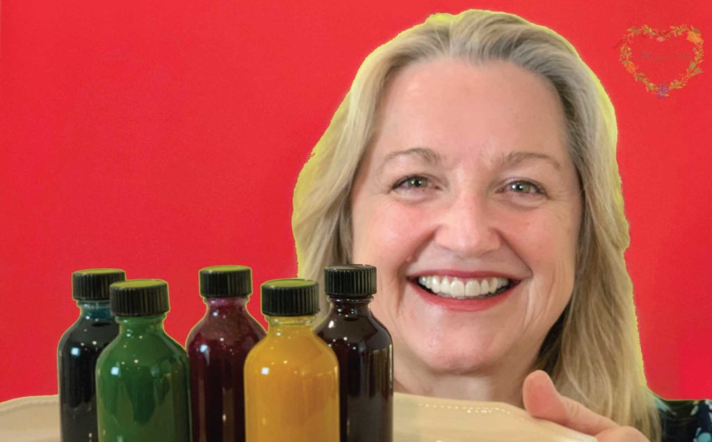 Mary holding vials of natural food coloring.