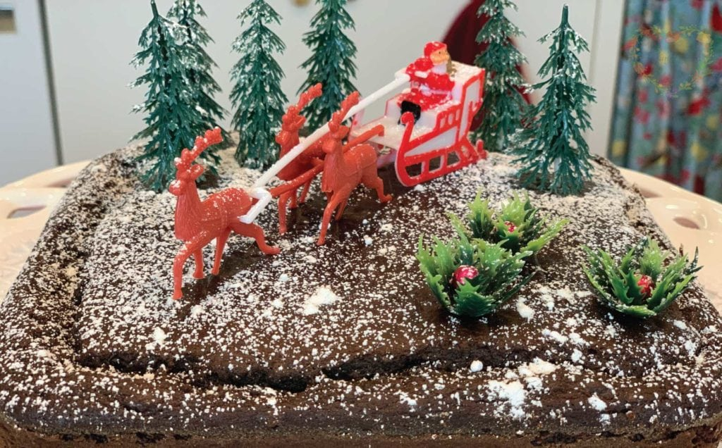 Santa with his reindeer and trees on a gingerbread cake.