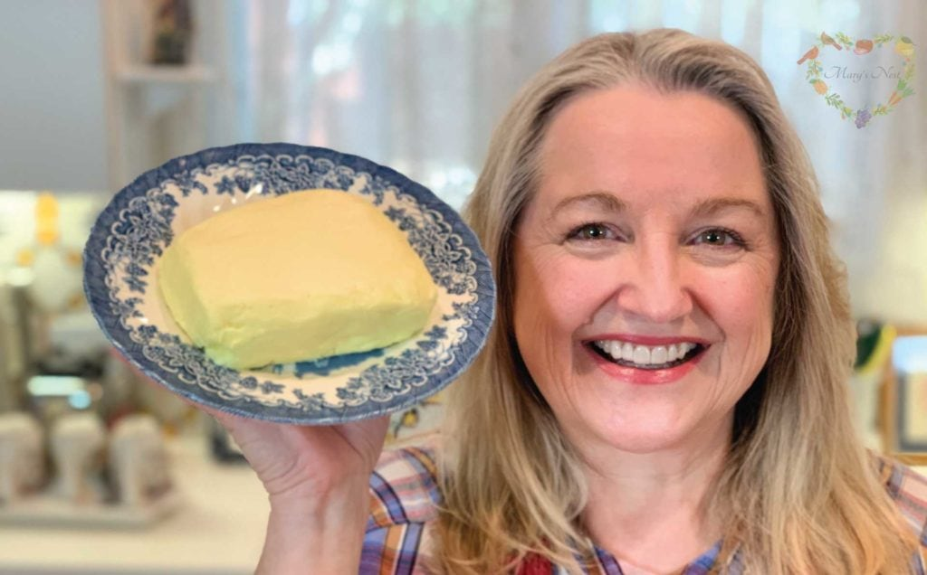 Mary holding a plate with homemade butter.