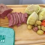 Corned Beef, Cabbage, Potatoes, and carrots on a tray with a St Patricks Day potholder.